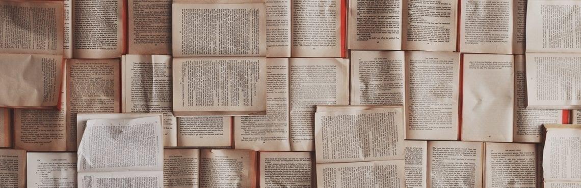 Bilden visar ett flertal uppslagna böcker.