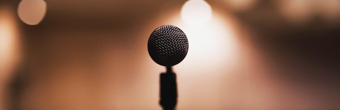 Bilden visar en mikrofon mot en suddig bakgrund.