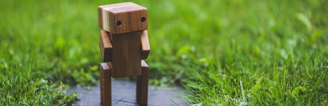 Bilden visar en robot i trä som står på en gräsmatta