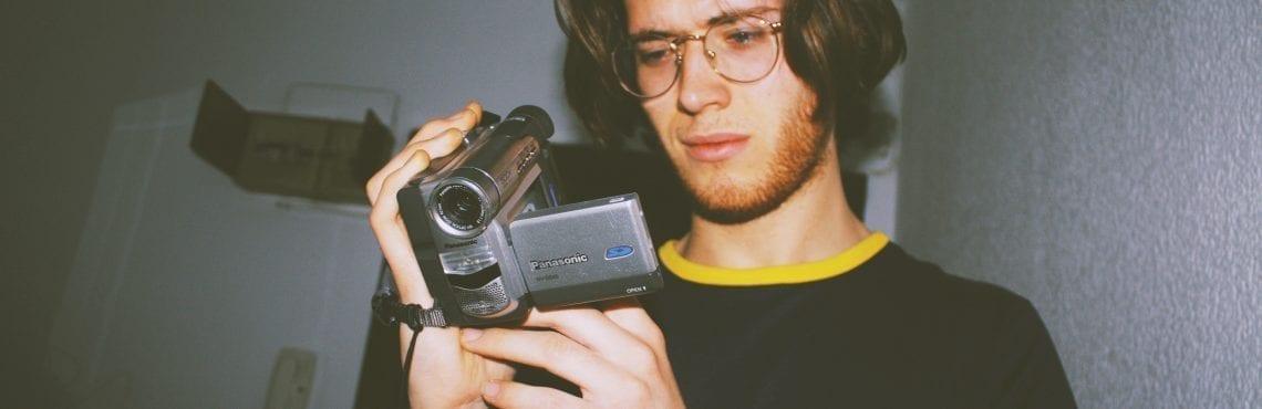 Bilden visar en man som tittar på en video i sin videokamera